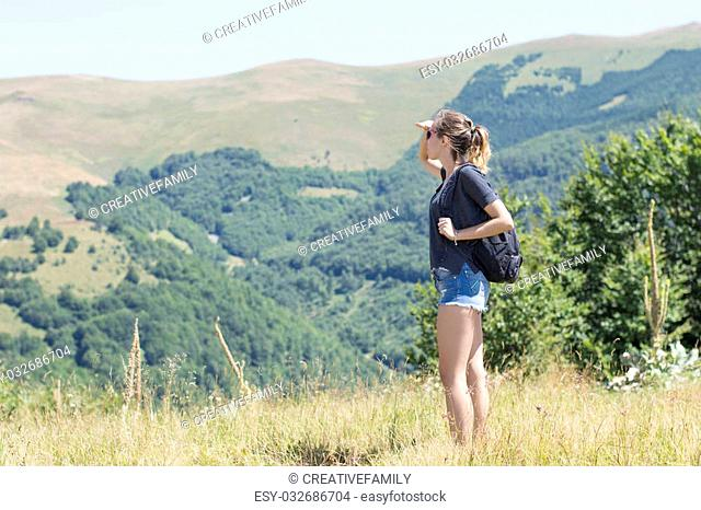 Young, beautiful girl with a backpack on her back, standing on the plateau. Green meadows and majestic mountains in the background