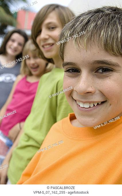 Portrait of a boy smiling with his friends leaning against a wall behind him