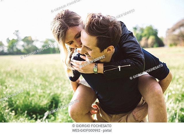 Man giving his girlfriend a piggyback ride