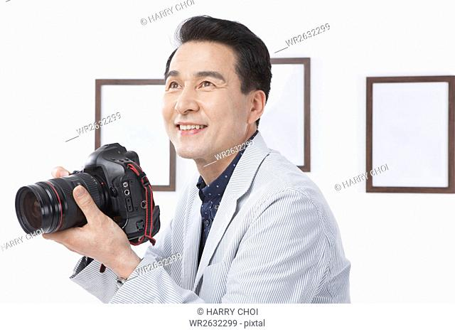 Portrait of smiling middle aged man holding a camera looking up against frames