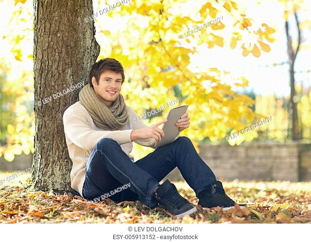 business, communication, modern technology and leisure concept - man with tablet pc in autumn park