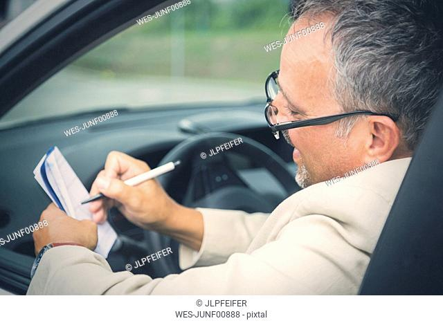 Businessman sitting in his car making notes
