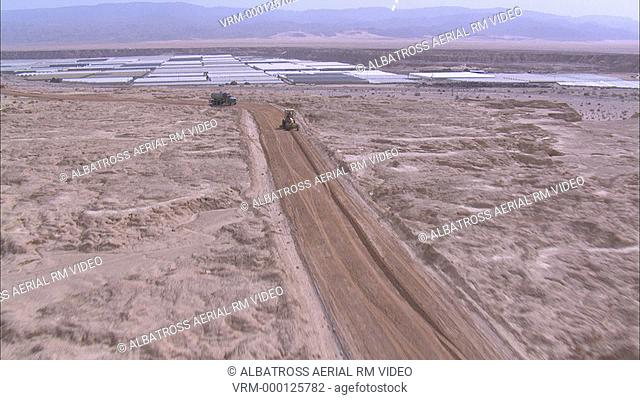 Aerial footage of Tractor in Desert and greenhouses