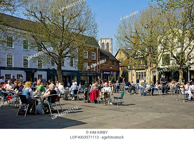 England, North Yorkshire, York. People sitting at tables outside cafes and restaurants in St Sampsons Square
