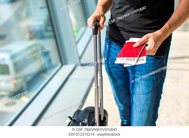 Man holding passports and boarding pass at airport while waiting the flight