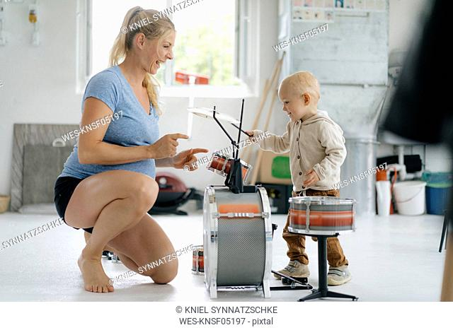 Happy pregnant mother with toddler son playing toy drums
