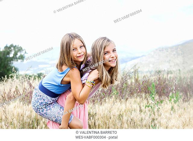 Spain, Girona, portrait of two happy sisters playing on a meadow