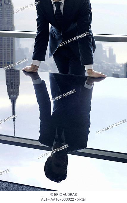 Businessman leaning against table, reflection in glass top