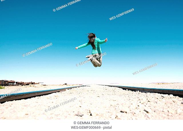 Bolivia, Uyuni train cemetery, woman jumping over the train tracks