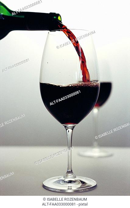 Red wine pouring into glass, close-up