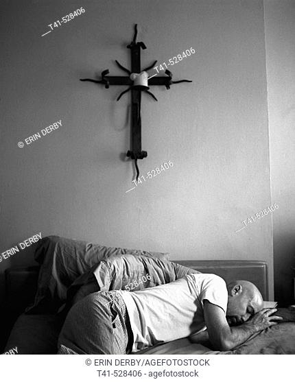 A man in his pajamas on his bed with an iron cross and candle above