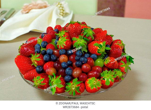 Fresh berries, blueberry, strawberry, raspberry in a glas bowl plate on gray table