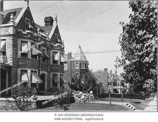 Angled view of homes on quiet street, cobblestone home with striped coverings for shade on windows, triangular shapes in top of homes, chimneys on top of homes