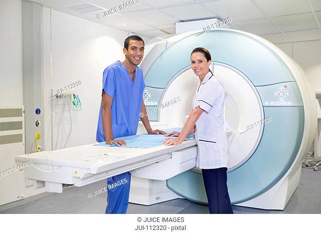 Portrait smiling technician nurses at MRI scanner in hospital