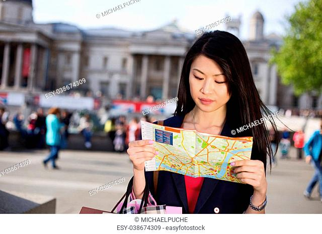 young chinese tourist reading a map in London