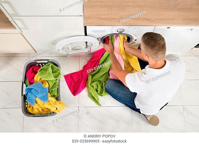High Angle View Of Young Man Using Washing Machine Appliance At Home