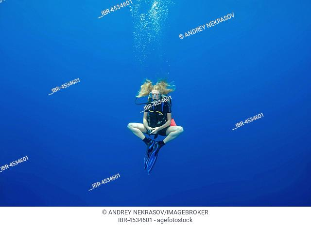 Female scuba diver hung in a lotus pose for a safety stop, in blue water, Indian Ocean, Maldives