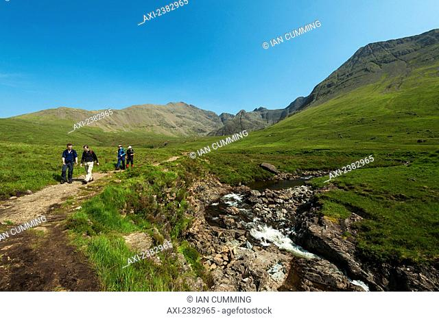 Walkers going past one of the Fairy Pools in Coire na Creiche, Black Cuillin; Isle of Skye, Scotland