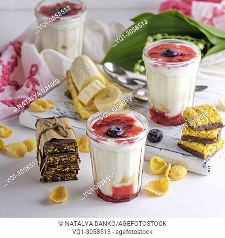 yogurt in transparent glass with syrup and banana on a white wooden background