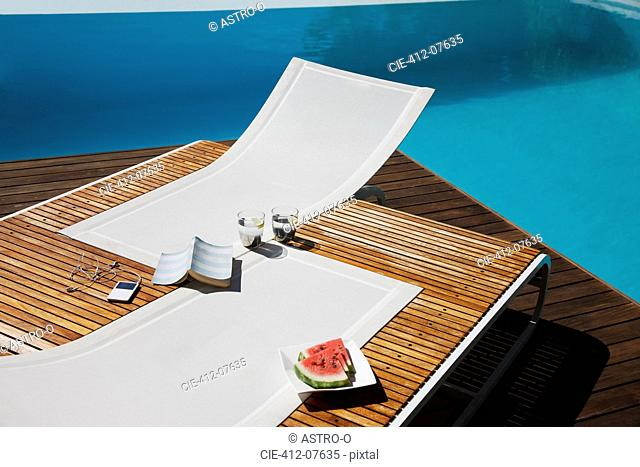 Book, mp3 player, water and watermelon on lounge chairs at poolside