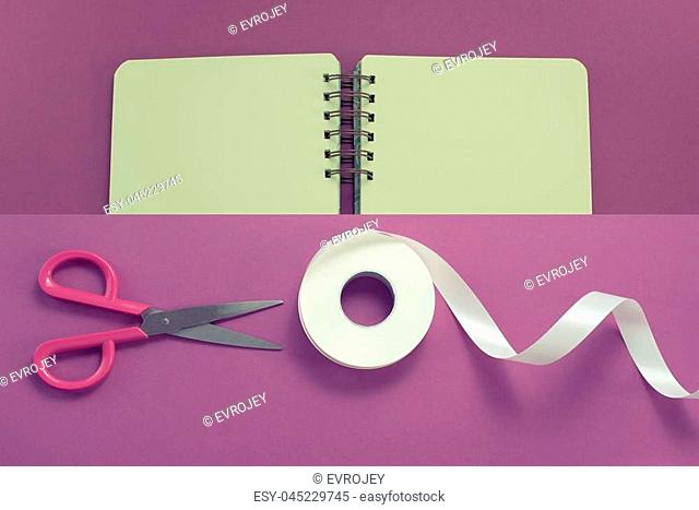 Collage Scissors and roll of tape in white on a purple background Opened the diary Materials for art, Hobby and design. Flat top view