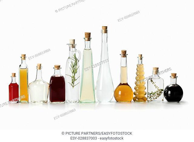 Row of bottles with homemade organic vinegar on white background