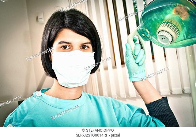Dentist adjusting lamp in office