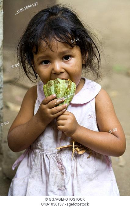 Young girl eating raw cacao pod