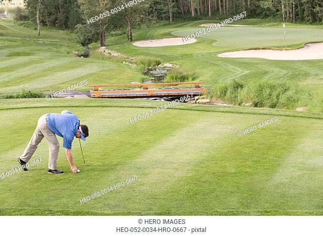 middle-aged male golfer placing ball on tee