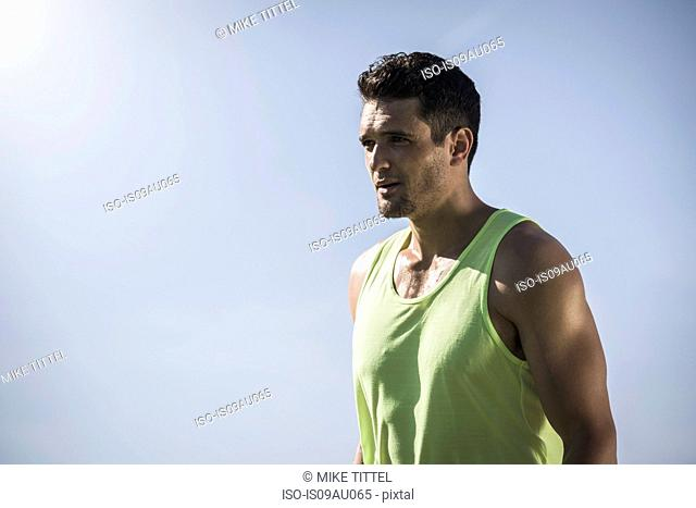 Portrait of confident athletic young man and blue sky