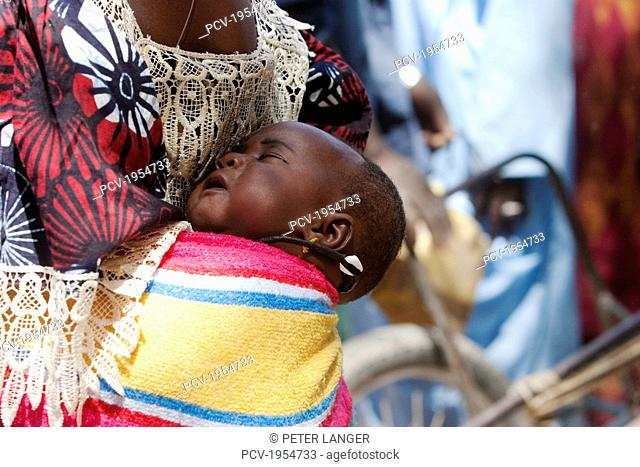Mother carrying baby on back in Djenne, Mali