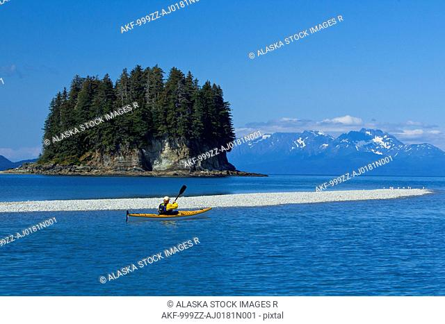 Sea kayaker paddles along the shoreline near Juneau with Coast Mountains in the background, Lynn Canal, Southeast Alaska, Summer