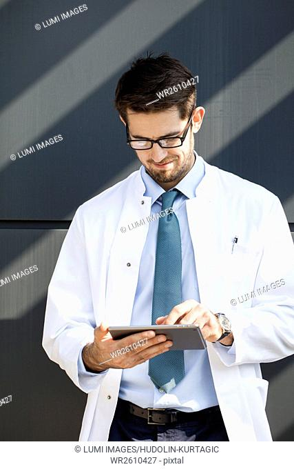 Doctor with eyeglasses using digital tablet outdoors