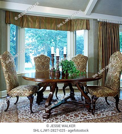 DINING ROOMS: Table and chairs in front of bay window, upholstered high back chairs, wood legs, round table with elaborate leg support