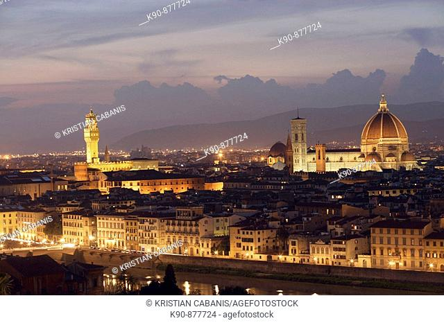 Aerial view of the old town of Florence with the Arno river and the bell tower of Palazzo Vecchio and the duomo (cathedral with campanile) at the early evening