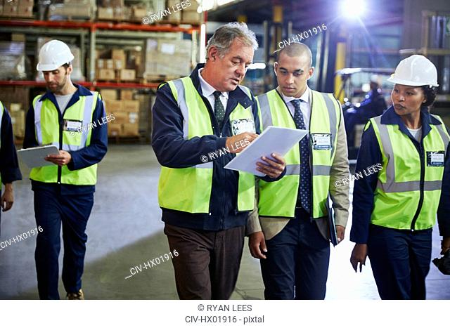 Manger and workers with clipboard talking in distribution warehouse