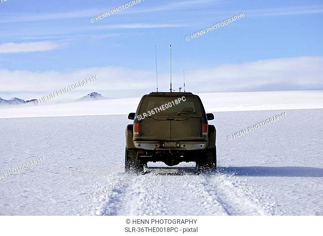 SUV driving on snow-covered glacier
