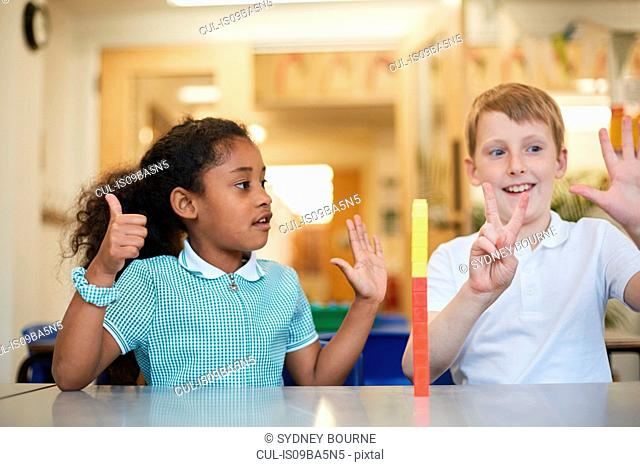 Schoolboy and girl counting on fingers in classroom at primary school