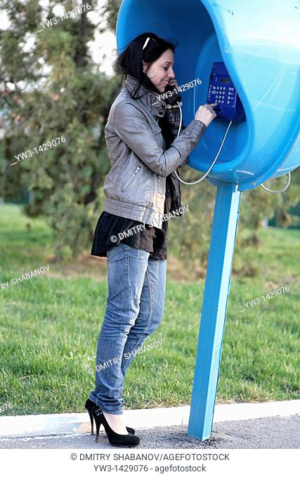beautiful brunette outdoor calling by street phone