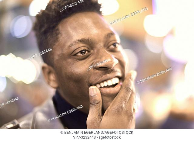 headshot of young man in city lights with positive mindset, African descent, looking aside, happy laughing, candid emotion, in Munich, Germany