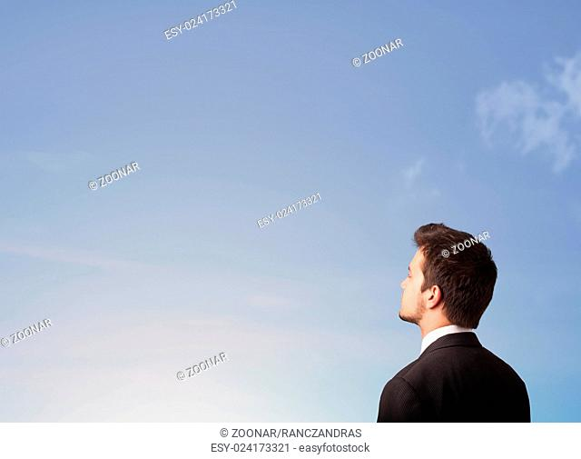 Handsome man looking at the blue sky copyspace