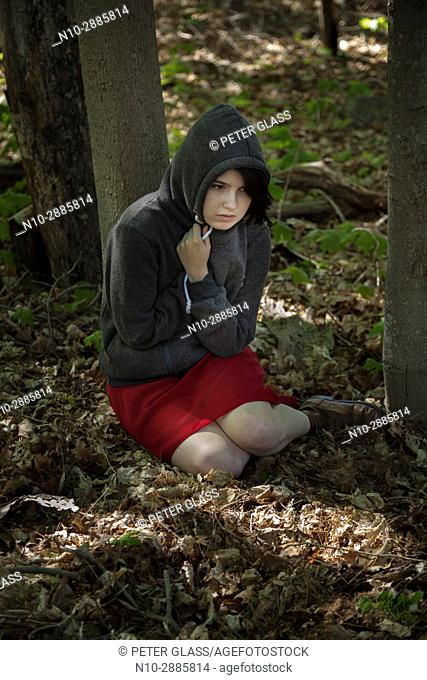 Young woman, sitting on the ground in a park, wearing a sweatshirt and hoodie