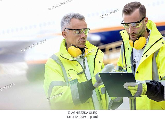 Air traffic controllers with clipboard talking on airport tarmac