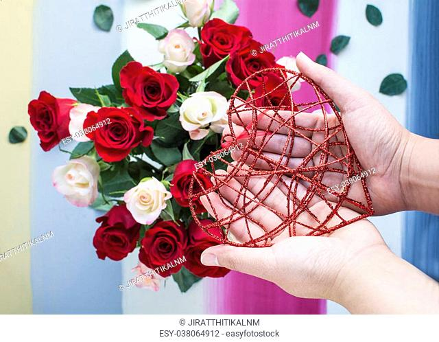 Hands holding glitter red metal heart with colorful painted and roses background