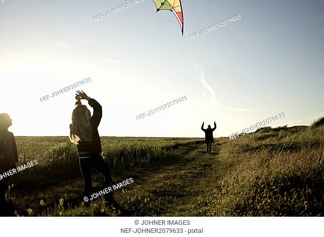 Girls with mother playing kite