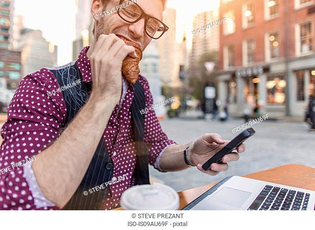 Stressed young businessman reading smartphone whilst eating at sidewalk cafe, New York, USA