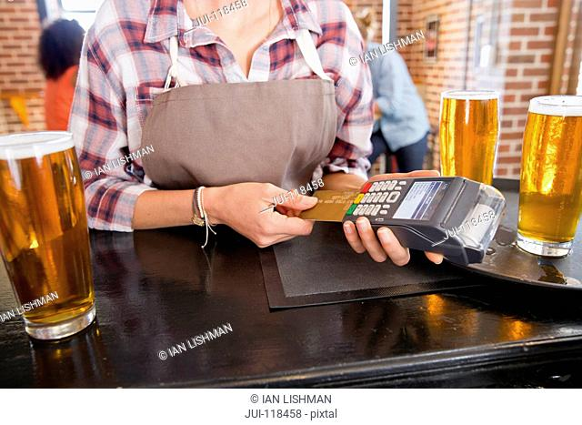 Waitress Processing Credit Card Payment In Bar