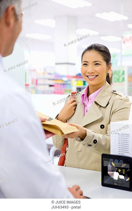 Female customer smiling and making a purchase in pharmacy