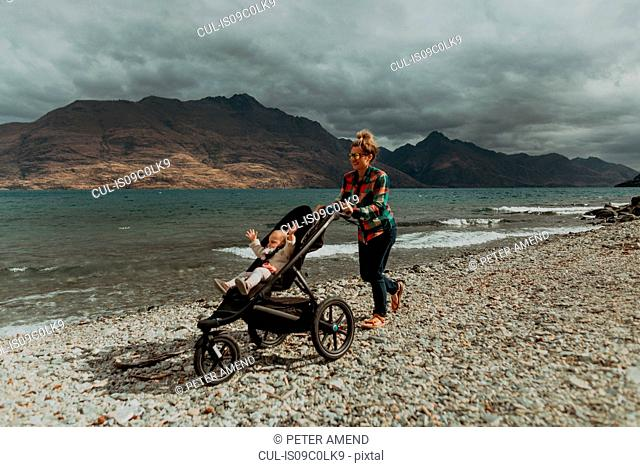 Mother with baby in pram walking on beach, Queenstown, Canterbury, New Zealand