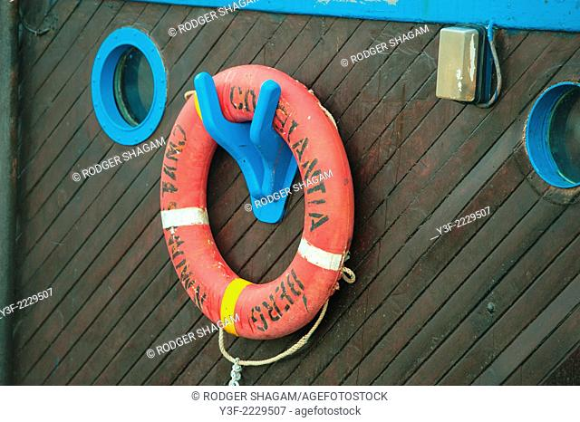 a section of a wooden bulkhead on a fishing trawler showing the life-saver ring as it is supported on easy access brackets